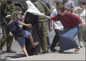 Settlers attacking a Palestinian woman while soldiers do nothing