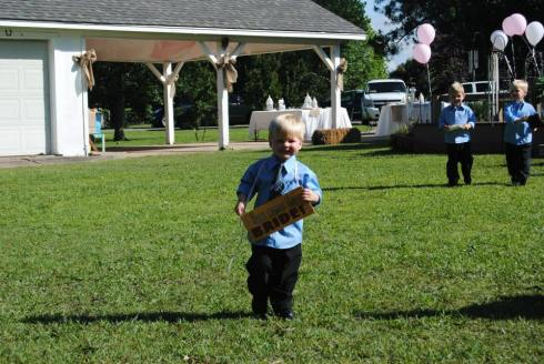 """Sign boy (the sign says """"Here comes the bride!"""") and ring bearers"""
