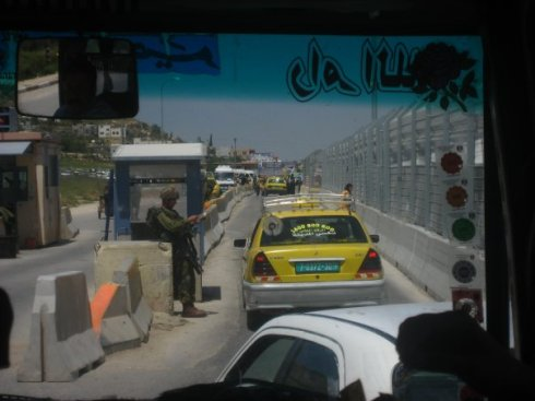 A car stopped at a checkpoint -- one of around 500 checkpoints, roadblocks, gates, and other barriers that hinder movement within the West Bank.