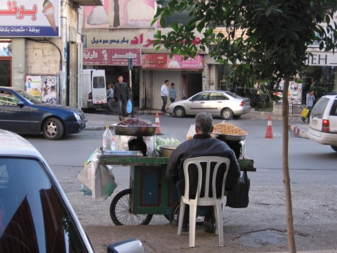 A man selling turmus (an edible seed) and other goodies on Ramallah's Main Street. In the upper left corner, you can see the sign for the famous Rukab's Ice Cream Shop.