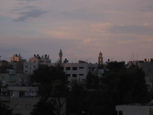 A minaret and church tower side by side in the Ramallah cityscape.